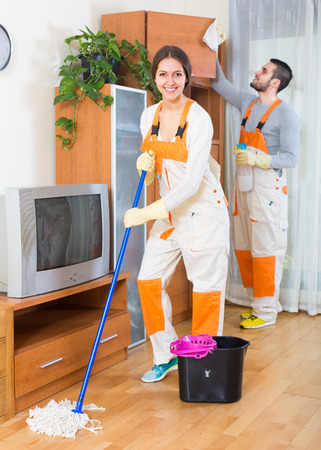 houseman: Professional cheerful cleaners cleaning in room