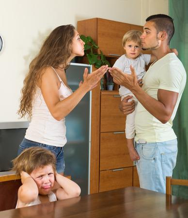 conflict: Hombre joven enojado con su esposa y sus dos hijos que tienen conflictos en el hogar