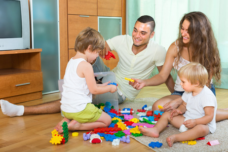 plastic toys: Happy family with two little children playing with plastic toys in home