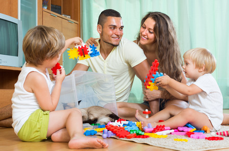 erector: Happy smiling parents and two daughters plays with meccano set in home