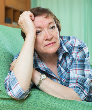 Portrait of sad mature woman having tough time and laying on couch photo