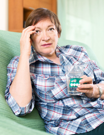 sad female pensioner with pills and glass of water indoor photo