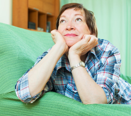 Stressed elderly female laying on her elbows and thinking indoor photo