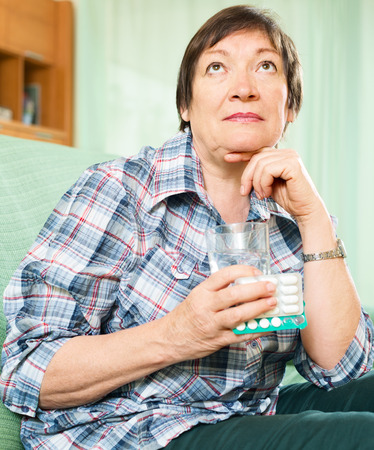 thinking mature woman with pills and glass of water indoor photo