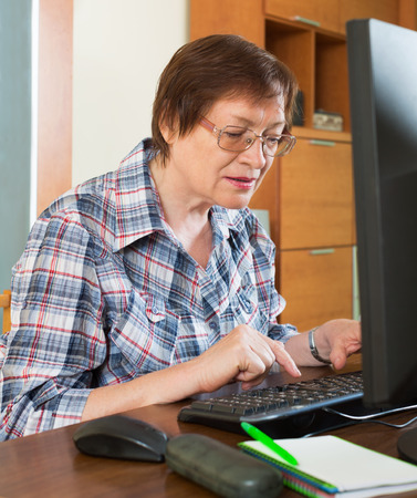 old people: Happy female pensioner working with personal computer in office interior