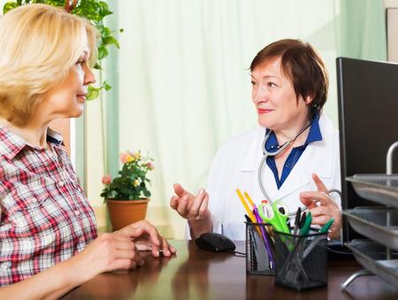 enfermera con paciente: Doctor de sexo femenino maduro que noticias positivas para un paciente