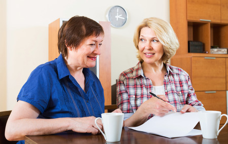 drawing up: Women notary officer helping aged client drawing up of will