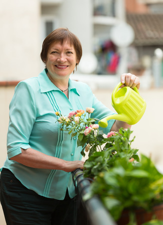 decorative balcony: Positive smiling senior woman watering decorative flowers on balcony