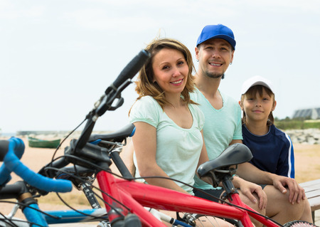 'cycles: Couple with teenager son sitting at seashore in summer day with cycles
