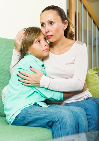 home comforts: middle-aged mother comforting teenage boy at living room
