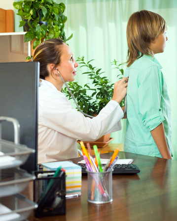 auscultoscope: Friendly female doctor with stethoscope examining teenage boy in clinic
