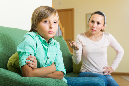 fracas: Mature mother and teenager son having conflict in home interior Stock Photo