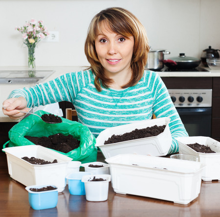 ordinary woman: Ordinary woman  making  ground  in pots for sprouts