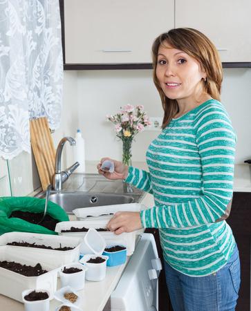 siembra: Mujer sonriente en los brotes verdes de siembra en la cocina de casa