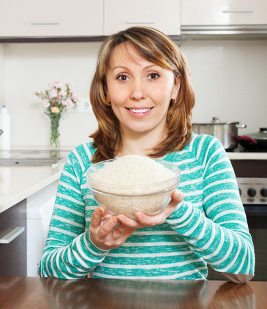 grits: Smiling  woman in green with rice grits at table in kitchen