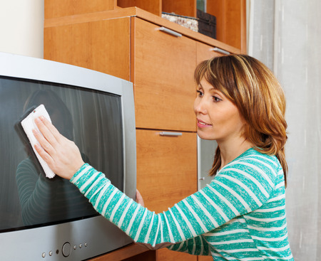 household tasks: woman in green wiping the dust on TV in living room Stock Photo