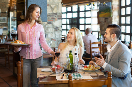 respectful: Portrait of happy adults people having dinner and respectful waiter