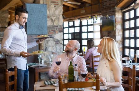 camarero: Retrato de las personas que tienen la cena y el camarero respetuosa Foto de archivo