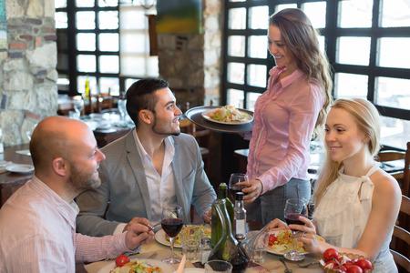 waiter serving: Smiling brunette female waiter serving restaurant guests. Selective focus