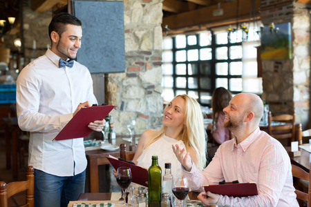respectful: Happy adults people having dinner and respectful waiter