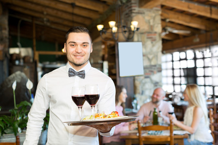 waiter: Portrait of a cheerful male waiter with a tray in his hand at the restaurant