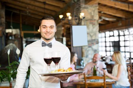 meseros: Retrato de un camarero masculino alegre con una bandeja en la mano en el restaurante