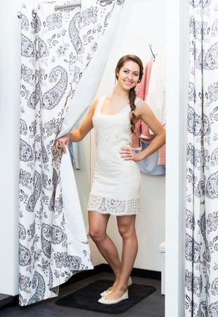 brune: Attractive smiling girl trying on new dress at apparel store