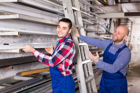 toolroom: Workmen in a warehouse are taking an aluminum window frame from a rack Stock Photo