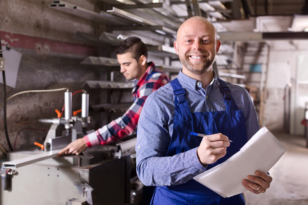 factory workers: Positive  worker operating in lathe, his boss with papers nearby