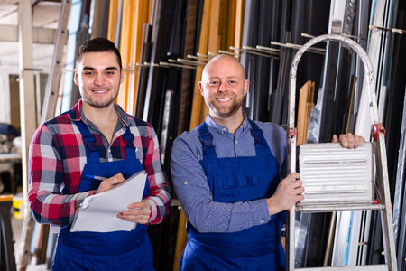 glasswear: Two smiling production workers in coverall with different PVC window Stock Photo