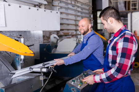 30 years old: Couple of 30 years old workers near milling machine at factory