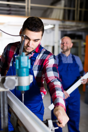 toolroom: Workers cutting aluminum frames on a lathe on a window production facility Stock Photo