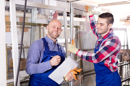 skilled operator: Satisfied manager approving employee work at PVC windows factory. Focus on the left man Stock Photo
