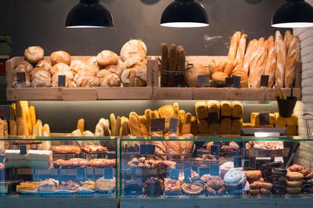 Moderne bakkerij met verschillende soorten brood, gebak en broodjes Stockfoto