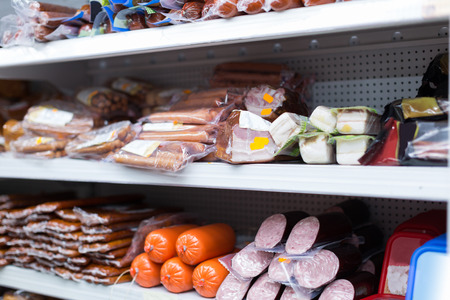 Refrigerator shelves with different meat products photo