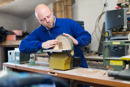 toolroom: Skilled professional woodworker working on a machine at guitar workshop