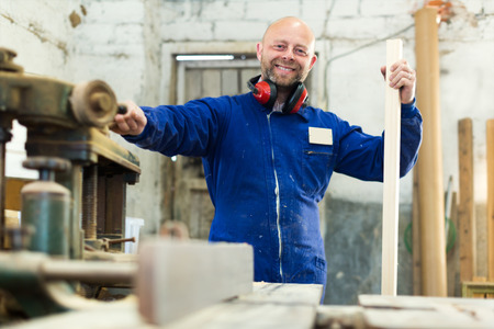 workroom: Male  worker on lathe at  wood workroom
