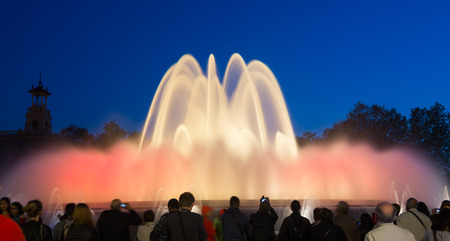 BARCELONA, SPAIN - APRIL 17, 2015: Evening view at colorful vocal fountain Montjuic show and people watching it nearby in Barcelona.  Catalonia