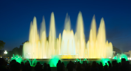 gazer: Evening view at colorful vocal fountain Montjuic show and people watching it nearby in Barcelona. Spain