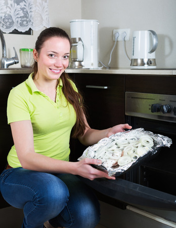 panful: Smiling young girl putting fish in oven at home kitchen