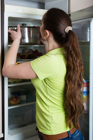 carefully: Young brunette woman carefully inspecting refrigerator shelves indoors