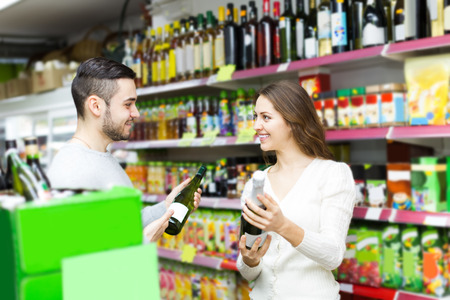 clothing store: Adult positive european shoppers choosing bottle of wine at liquor store Stock Photo