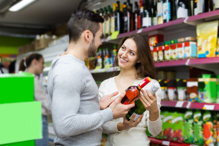 store: Adult smiling european shoppers choosing bottle of wine at liquor store