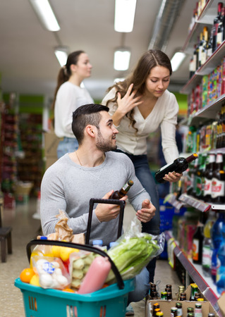 alcoholic beverages: Mixed gender customers at a liquor store buying alcoholic beverages