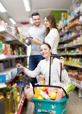 canned goods: Cheerful group people standing near shelves with canned goods at shop Stock Photo