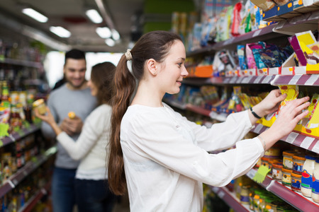 canned goods: Cheerful people standing near shelves with canned goods at shop Stock Photo