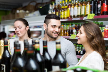 People in a liquor store are buying wine at a discount photo
