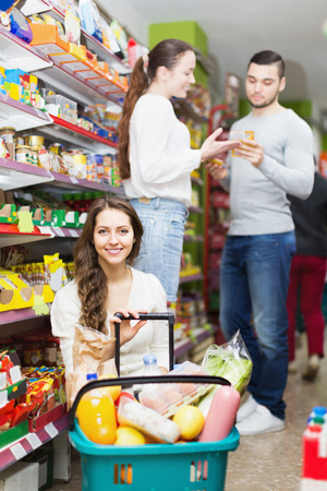 Smiling young adults choosing tinned food at supermarket photo