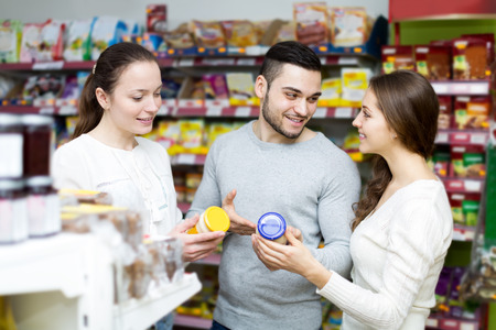 Portrait group of young people to choose canned in grocery store photo