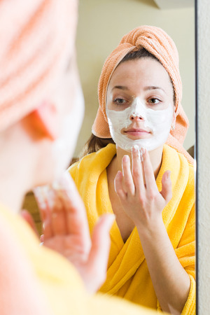 house robes: Female in bathrobe treating skin with face pack in front of the mirror Stock Photo